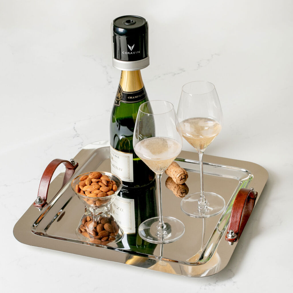 A silver tray with glasses of wine and a bowl of nuts