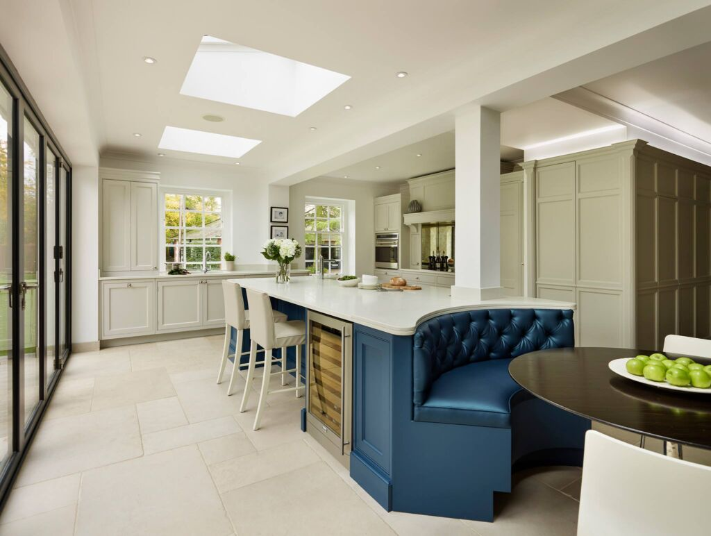 A spacious light and airy kitchen with blue leather seating