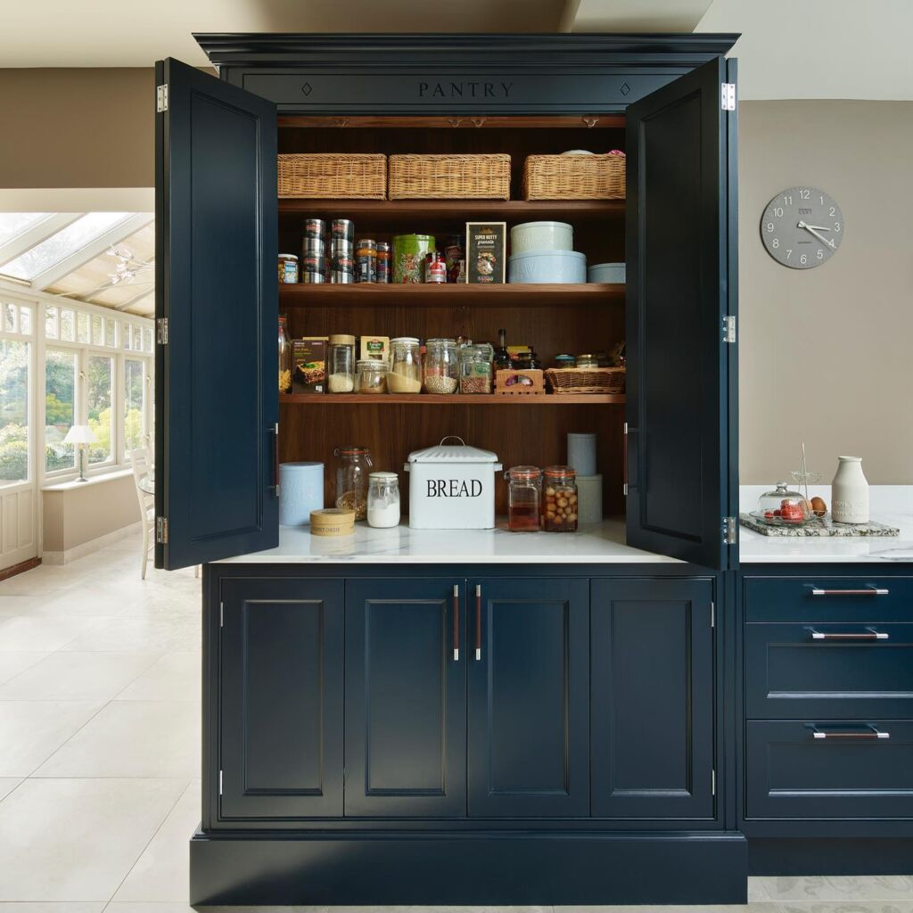 A bespoke dark blue kitchen pantry designed by Davonport and filled with jars and food