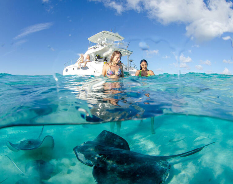 Young ladies meeting stingrays in the Cayman Islands seas