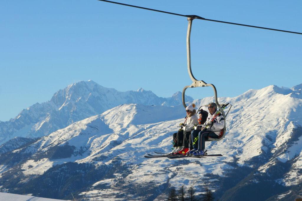 A family of three taking a trip on a ski lift